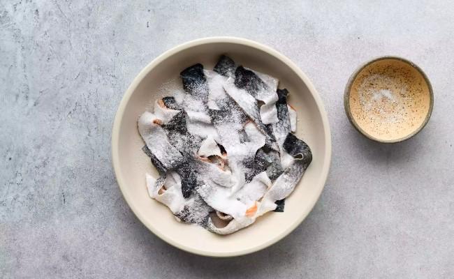 Cho da cá hồi vào bát và rắc muối lên